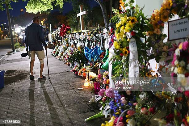 Monte Talmadge walks past the memorial on the sidewalk in front the Emanuel African Methodist Episcopal Church after a mass shooting at the church...