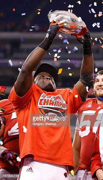 Montee Ball of the Wisconsin Badgers holds up the Stagg Championship Trophy after beating the Nebraska Cornhuskers 70-31in the Big 10 Conference...