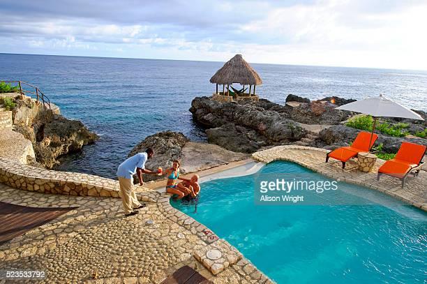 montego bay, jamaica. couple having drinks at the pool - località turistica foto e immagini stock