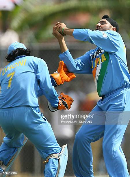 Indian cricket players Harbhajan Singh and Mahendra Dhoni collide as Singh catches a ball to dismiss Jamaican batsman Damion Ebanks during a one day...