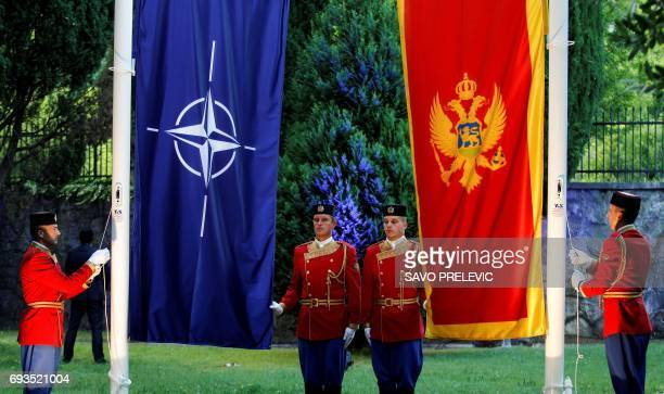 Montenegrin honour guards raise NATO and Montenegrin flags during a ceremony in the capital Podgorica on June 7 2017 Montenegro became NATO's 29th...