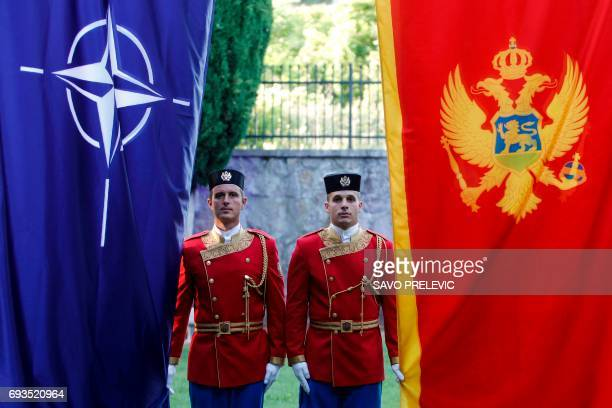 Montenegrin honour guards stand next to NATO and Montenegrin flags during a ceremony in the capital Podgorica on June 7 2017 Montenegro became NATO's...