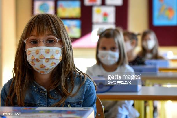 Montenegrin schoolchildren wearing protective masks to prevent the spread of the novel coronavirus , take part in a course on the first day of the...