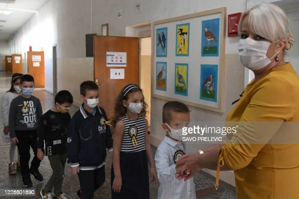 Montenegrin schoolchildren wearing protective masks to prevent the spread of the novel coronavirus wait in line with their teacher on the first day...