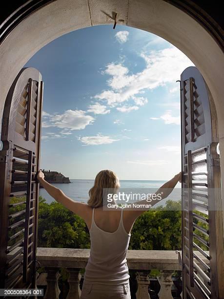 Montenegro, Sveti Stefan, woman opening shutters, rear view