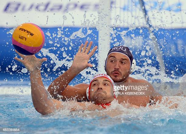 Montenegro's Filip Klikovak fights for the ball with Romania's Dan Andrei Busila during the men's Water Polo European Championships match of...
