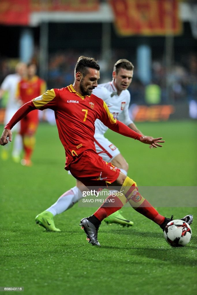 Montenegro's Marko Vesvic (L) vies with Poland's Lukasz Piszczek during the FIFA World Cup 2018 qualification football match between Montenegro and Poland in Podgorica on March 26, 2017. /