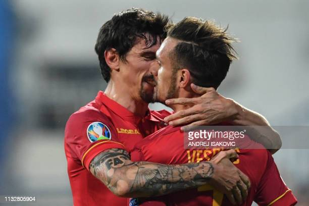 Montenegro's midfielder Marko Vesovic is congratuled by Montenegro's defender Stefan Savic after scoring the first goal of the Euro 2020 football...