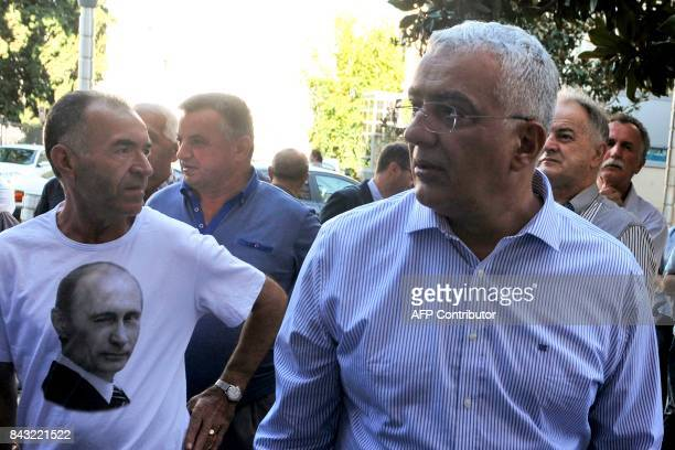 Montenegro's opposition Democratic Front leaders Andrija Mandic stands next to a supporter wearing a tshirt with a picture of Russian President...