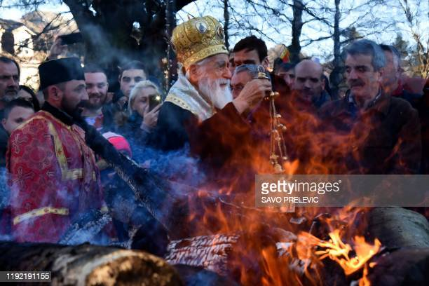 Montenegro's Orthodox Church Archbishop Mihailo attends a ceremonial burning of dried oak branches the Yule log symbol for the Orthodox Christmas Eve...