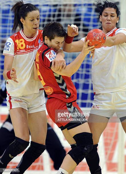 Montenegro's pivot Ana Dokic is pushed by Spain's Begona Fernandez and Veronica Cuadrado during the 2012 EHF European Women's Handball Championship...