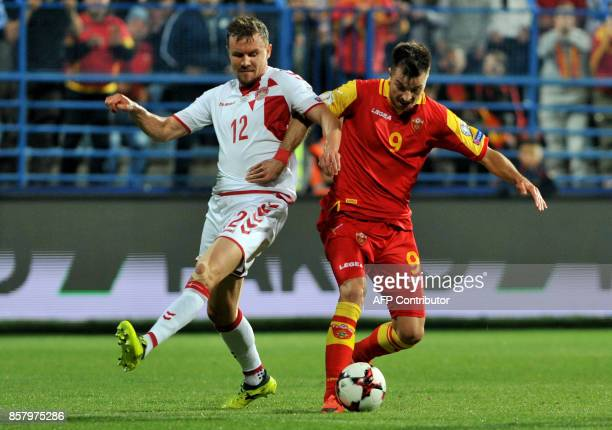 Montenegro's Stefan Mugosa fights for the ball with Denmark's Andreas Bjelland during the FIFA WC 2018 Group E football qualification match between...