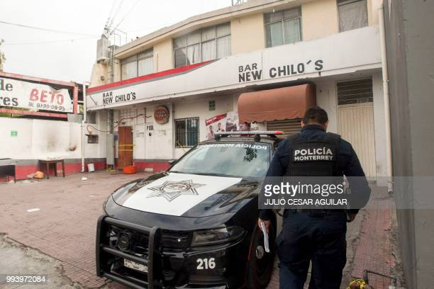 A Monterrey police officer guards a bar where people were murdered at dawn in a simultaneous attack in Monterrey Nuevo Leon Mexico on July 8 2018 At...