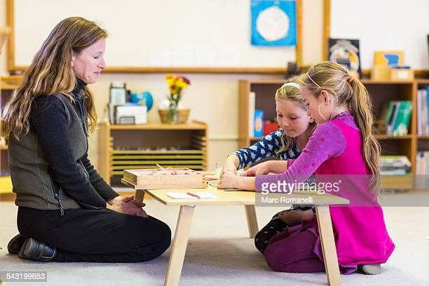 montessori teacher helping students in classroom - montessori education stock pictures, royalty-free photos & images