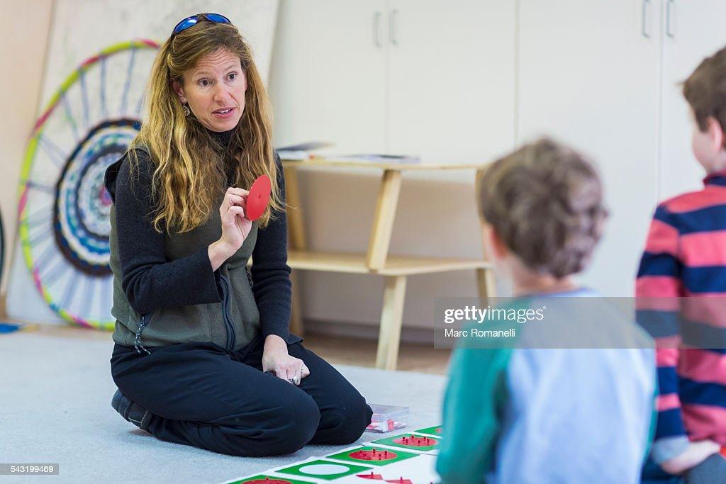 Montessori teacher talking to students in classroom : Stock Photo