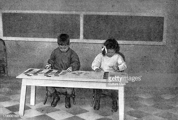 Montessori teaching method early 20th century Children working with language cards Educational approach developed by Italian physician and educator...