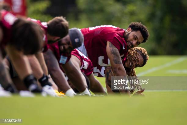 Montez Sweat and Chase Young of the Washington Football Team warm up with teammates during mandatory minicamp at Inova Sports Performance Center on...