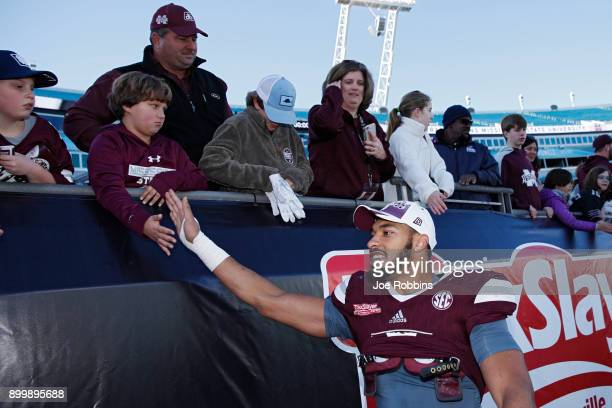 Montez Sweat of the Mississippi State Bulldogs celebrates with fans following the TaxSlayer Bowl against the Louisville Cardinals at EverBank Field...