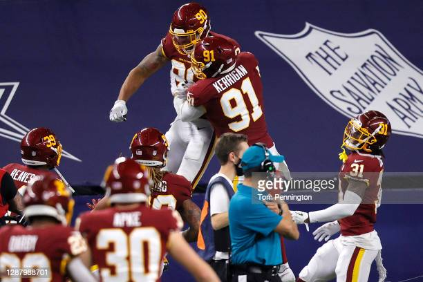 Montez Sweat of the Washington Football Team celebrates an interception for a touchdown along with Ryan Kerrigan during the fourth quarter of a game...