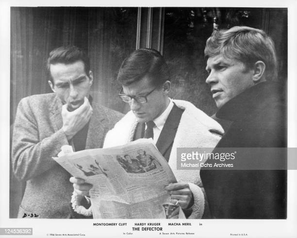 Montgomery Clift Roddy McDowall and Hardy Kruger reading the paper in a scene from the film 'The Defector' 1966