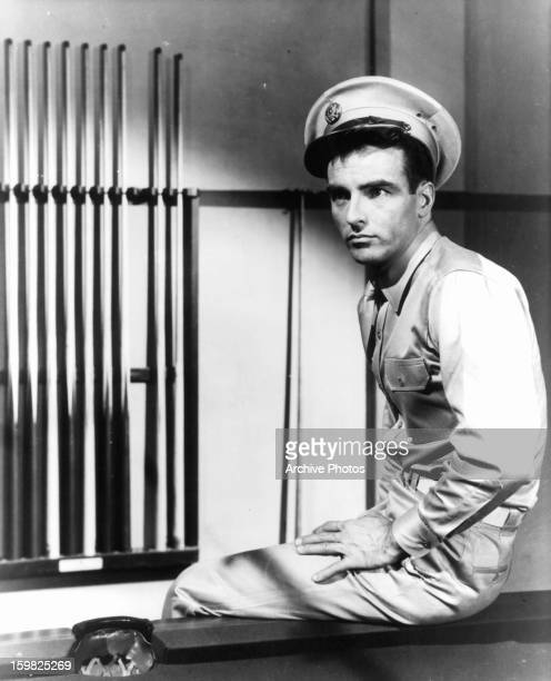 Montgomery Clift sits on a pool table in a scene from the film 'From Here To Eternity' 1953