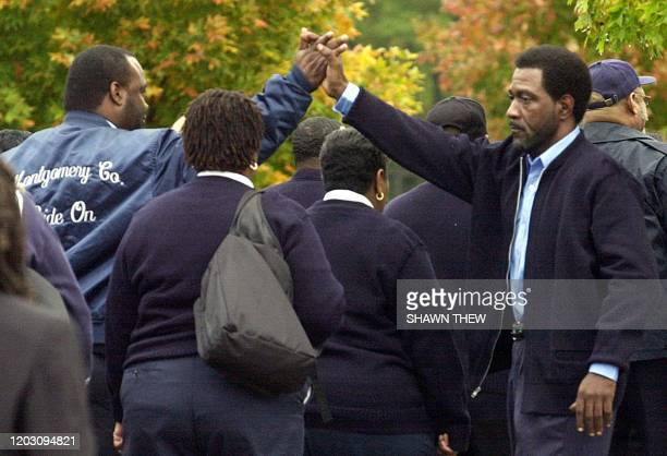Montgomery County Ride On bus drivers hold hands as they arrive for the funeral services of 35-year-old driver Conrad Johnson 26 October, 2002 at...