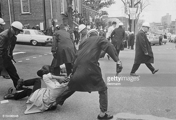 Montgomery police drag African American protesters practicing passive resistance down Dexter Avenue where several of them lay down Four were arrested