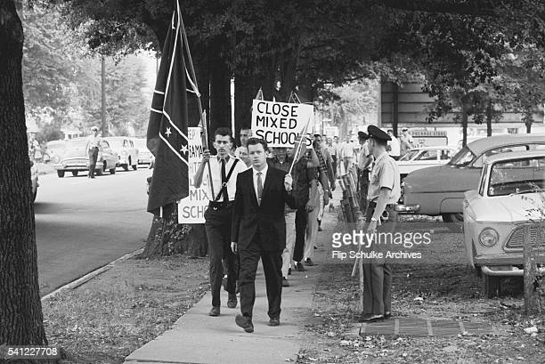 Montgomery police keep protesters against school desegregation on the sidewalk around a public school