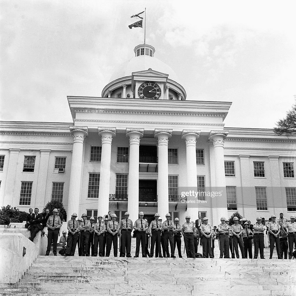 Montgomery police stand in front of the Alabama State Capitol at the end of the Selma to Montgomery March, Montgomery, Alabama, March 25, 1965. The building served as the first capitol of the Confederacy until May 22, 1861. On February 18, 1861, Jefferson Davis took his oath of office on the front portico as the only President of the Confederate States of America. The Confederate and Alabama flags fly over the Capitol.
