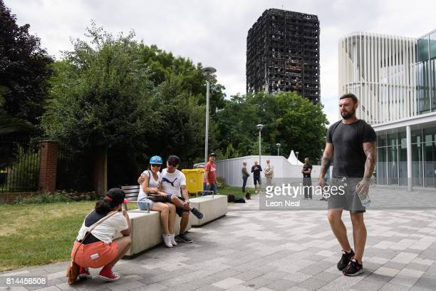 A month after a massive fire claimed the lives of at least 80 people residents look on as tourists pose for photographs in front of the remains of...