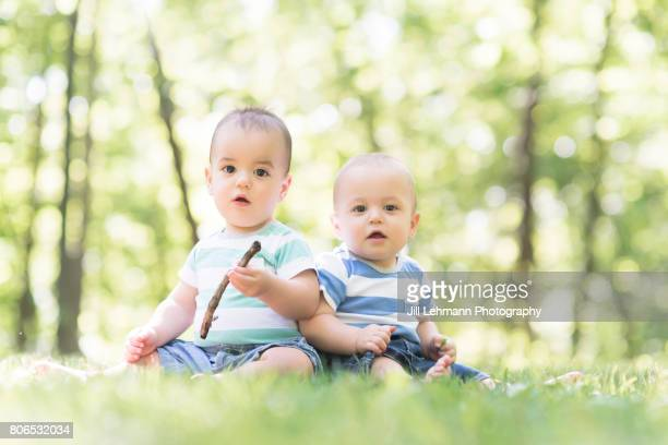 12 month Beautiful Fraternal Twin Babies Sits in Nature Together