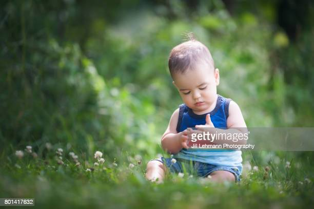 12 month Beautiful Fraternal Twin Baby Sits in a Park