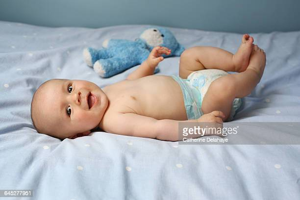 A 4 month old baby boy laying on a bed