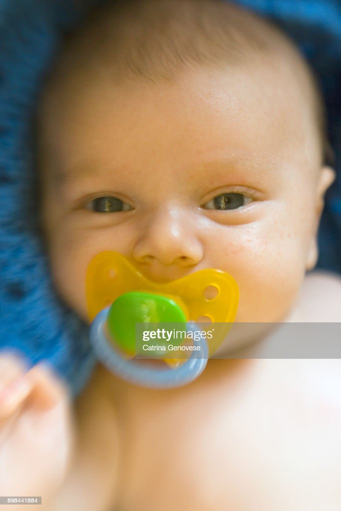 2 month old baby boy with pacifier in mouth on blue blanket stock