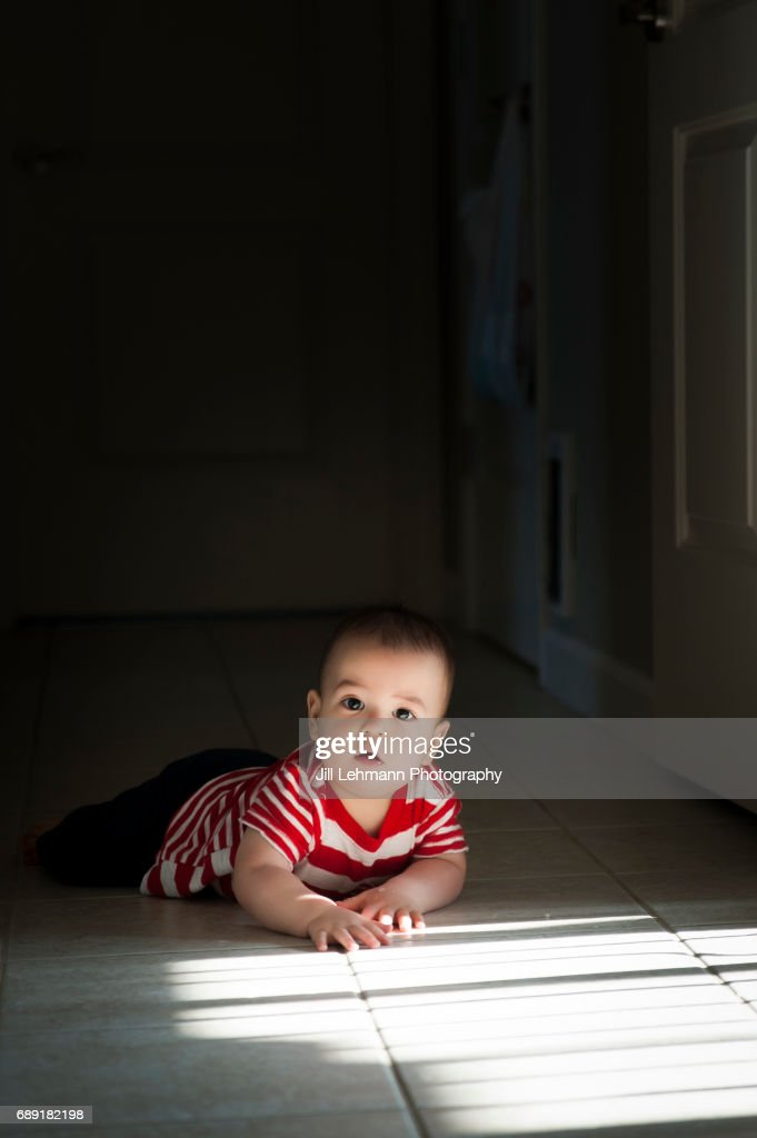 12 Month Old Baby Crawls In Sunlight : Stock Photo