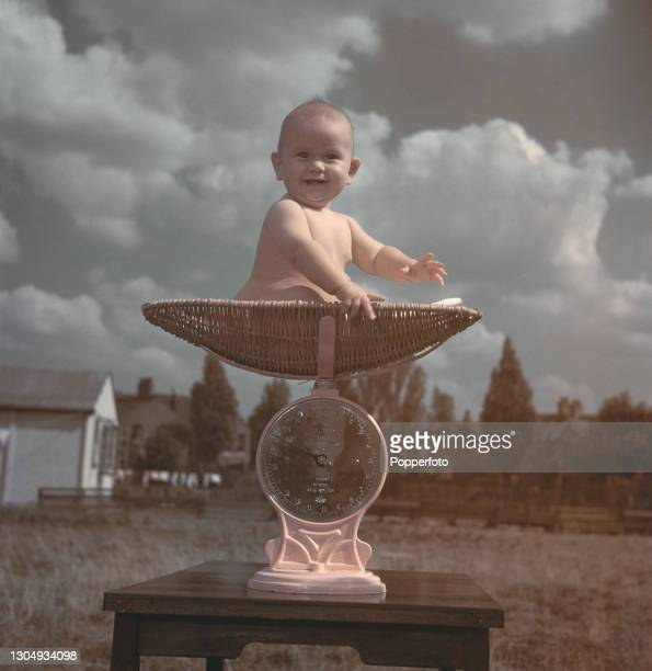 Month old baby girl is weighed on a set of scales in the open air in England in September 1947.