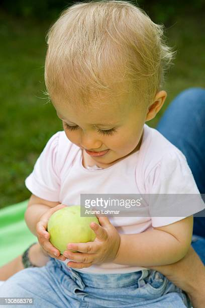A 10 month old baby girl playing with an apple