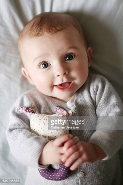 a 5 month old baby girl smiling - delahaye stock photos and pictures