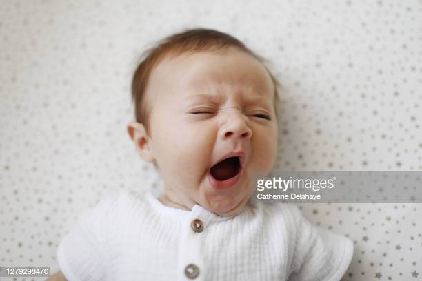 a 4 month old baby girl yawning - yawning stock pictures, royalty-free photos & images