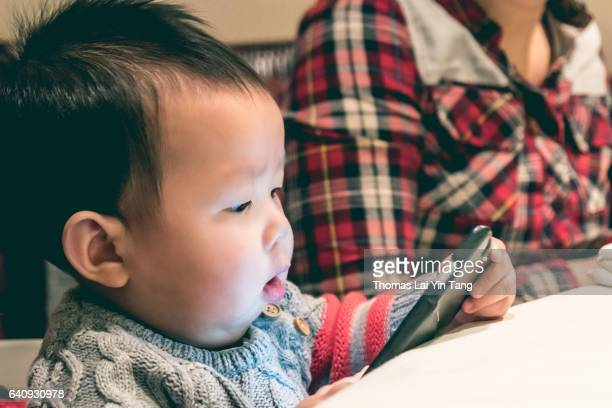 8 month old baby holding mobile phone for the first time. - my lai sit fotografías e imágenes de stock
