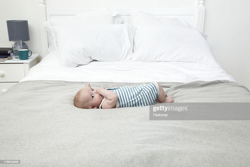 3 month old baby lying on bed : Stock Photo