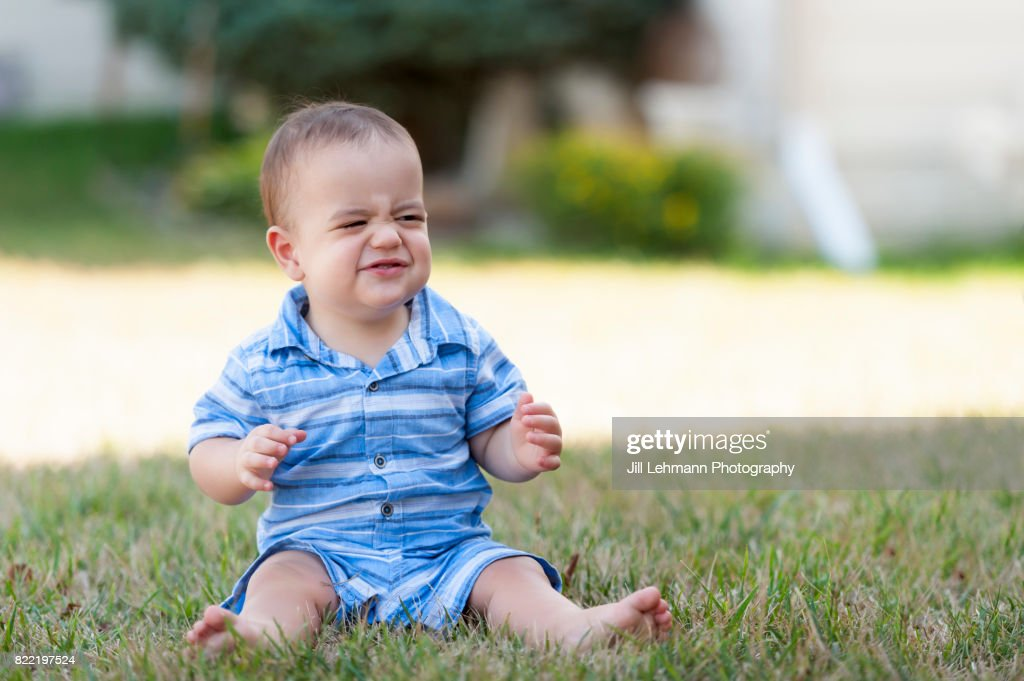 12 Month Old Baby Makes a Funny Face and While Showing His Muscles : Stock Photo