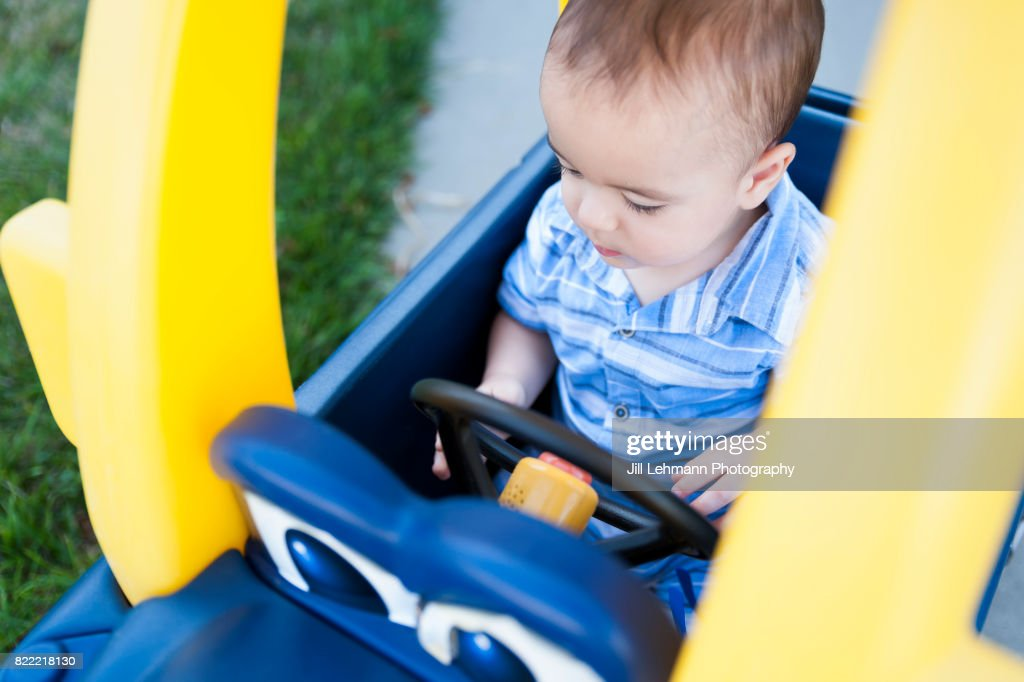 12 Month Old Baby Plays in Plastic Toy Car and Pretends to Drive : Stock Photo