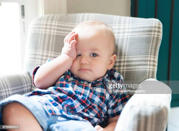 12 month old baby sits in a children's chair looking stressed - fruncido fotografías e imágenes de stock