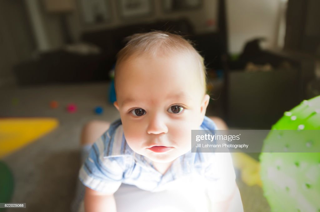 12 Month Old Baby Stares At Camera Playing at Home : Stock Photo