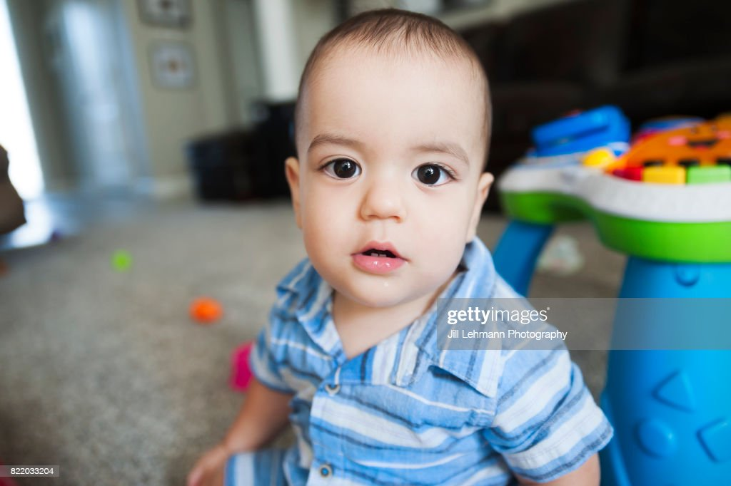 12 Month Old Baby Stares At Camera While Playing at Home : Stock Photo