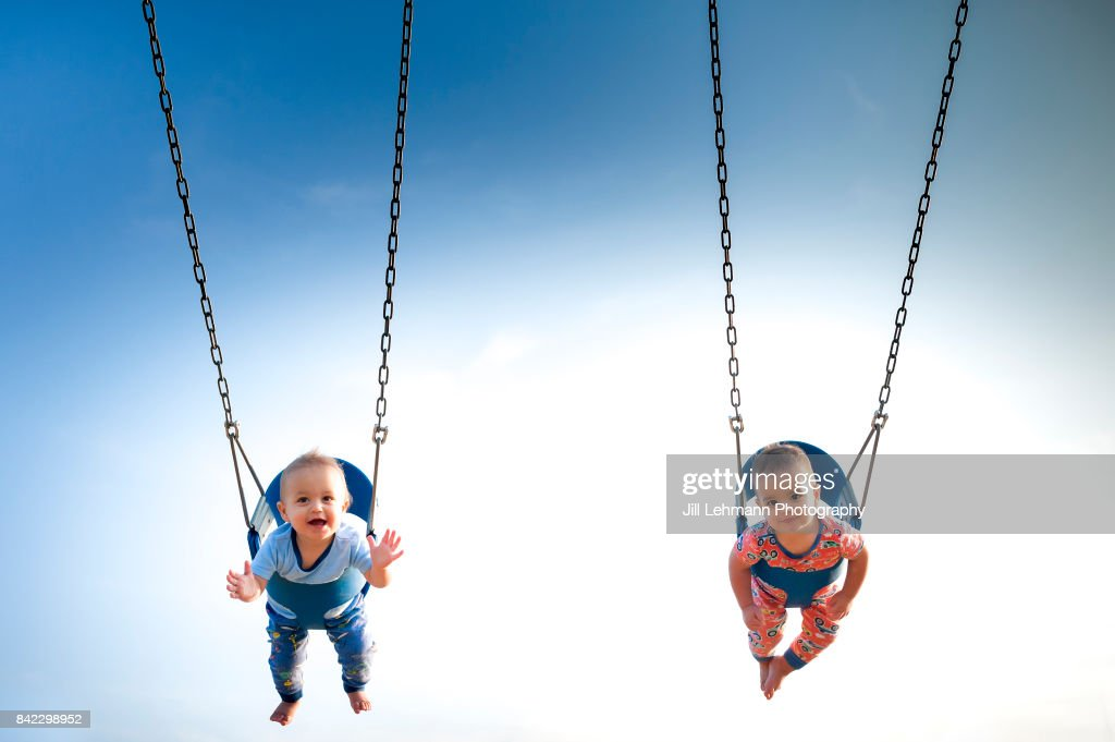 12 Month Old Fraternal Boys Swing in Pajamas at a Park : Stock Photo