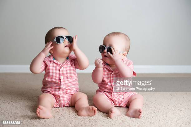 11 month old fraternal twin boys play together with sunglasses - cute twins stock photos and pictures