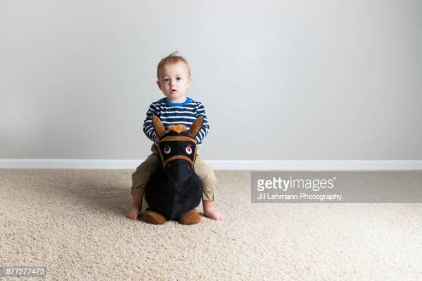 15 month old fraternal twin in stripes rides a tony pony at home - one baby boy only stock pictures, royalty-free photos & images
