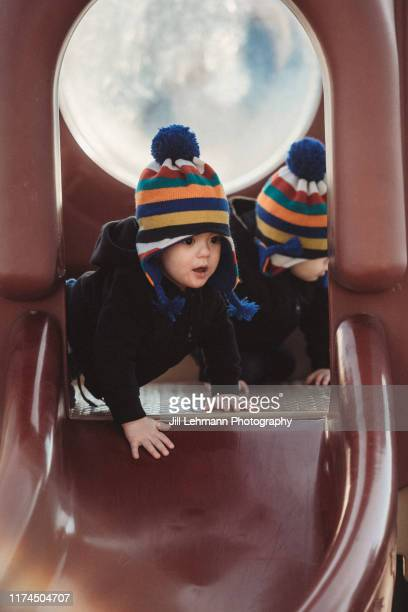 18 month old fraternal twin toddlers play on a slide at public park in early spring - slide play equipment stock pictures, royalty-free photos & images